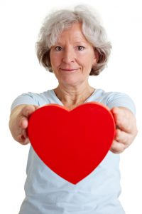 Glückliche Rentnerin hält ein großes rotes Herz