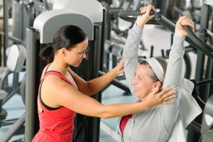 Senior woman exercise on shoulder press machine with personal trainer